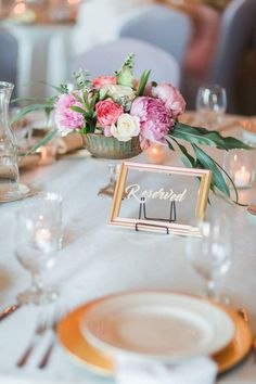 """Bright floral centerpiece with gold calligraphied """"reserved"""" sign"""