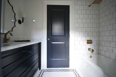 Meredith Heron Design - bathrooms - black and white bathroom, black door, drop in tub, gold shower kit, white square tile shower surround, black sink vanity, white marble countertop, gold faucet, brass scalloped mirror, black and white hex tiled floor