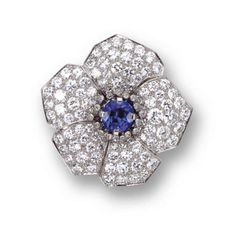 DIAMOND AND SAPPHIRE FLOWER BROOCH, CARTIER,  1937.   The flowerhead set in the center with a round sapphire weighing approximately 2.45 carats, the petals pavé-set with 100 round and single-cut diamonds weighing approximately 7.00 carats, mounted in platinum, signed Cartier, inscribed: F.D.F. Xmas 1937.