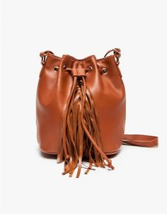 Soft faux leather bucket bag with modern accents. Features top drawstring closure, gold-toned hardware, adjustable shoulder strap and side fringe detailing.   	•	Faux leather bucket bag 	•	Adjustable shoulder strap 	•	Top drawstring closure 	•	Side f