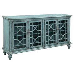 Showcasing a distressed bayberry blue finish and glass-paneled doors with fretwork overlay, this stylish sideboard is perfect in your living room or den.