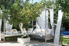 Painter Olivier Mourao devised a dreamy seating area at his Ibiza oasis using a white sofa and flowing curtains to add a touch of privacy.
