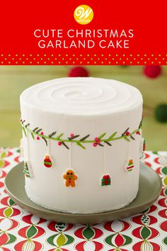 "This Cute Christmas Garland Cake is a fun and festive way to celebrate Christmas with the family this year! Simply ice your cake with buttercream, then use a cake marker to make a line around your cake for the garland. After piping the leaves and berries, you can add cute ""ornaments"" using dot matrix icing decorations. A fun cake to make with the kids, this garland cake is a treat (almost) too cute to eat! #wiltoncakes #christmascake #cakedecorating #cakeideas #homemade #baking…"