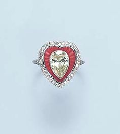 A CORAL AND DIAMOND RING   Centering upon a pear-shaped diamond, within a heart-shaped fluted coral plaque, to the circular-cut diamond trim, and similarly-set shoulders, mounted in platinum. [Unusual]