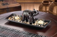 A touch of African style turns two simple candles into dramatically fantastic decor! A carved elephant statue stands guard over a collection of polished rocks and two clear glass candle cups, all set Candle Cups, Candle Set, Tea Light Candles, Tea Lights, Glass Candle, Clear Glass, Safari Living Rooms, Living Room Decor, African Theme