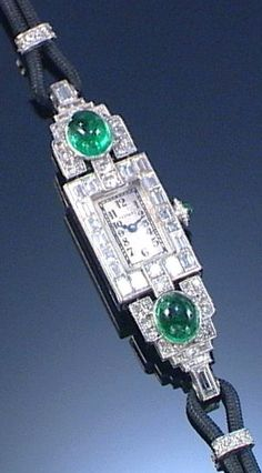 LADY'S EMERALD AND DIAMOND COCKTAIL WATCH, 1930S The rectangular dial applied with Arabic numerals within a bezel millegrain-set with step-cut diamonds, the articulated shoulders embellished with single-cut, baguette diamonds and two oval cabochon emeralds, to a cord strap, length approximately 160mm, dial signed Tessiers.