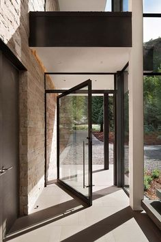 Dramatic stone and glass home in Aspen surrounded by forestLike the large glass pivot door and concrete floor Contemporary Mountain Home-Charles Cunniffe Kindesign Modern Front Door Designsfarebnost- 2 druhy dreva!Interior Design by Contemporary Front Doors, Modern Front Door, Modern Entryway, Entry Doors With Glass, Glass Front Door, Aluminium Front Door, Exterior Doors With Glass, Glass Doors, Door Design