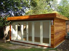 garden office room with full width folding doors and timber clad gable ends, still think random slit windows 1 vertical 1 horizontal to make interesting focal point