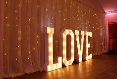 Large illuminated LOVE letters,  suitable for inside and outside use,  set against a pealight backdrop by stressfreehire.com #venuetransformers