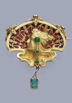 JOE DESCOMPS - An Art Nouveau 18K yellow gold, plique-à-jour enamel and emerald brooch. Depicting a woman's profile surrounded by orchid motifs decorated with an orange-red plique à jour enamel. The woman is wearing jewellery embellished with green enamel cabochons. The reversed engraved with the monogram of Joe Descomps, initials JD with a small spider below.