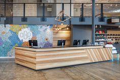 Austin Bouldering Project; Lilianne Steckel Interior Design; Sophie Roach mural; Industrial gym design; Reception desk; steel; oak; paperstone; concrete floors; welcome desk; wood cladding; teal; yellow; colorful mural; hand painted; bouldering gym; commercial design.
