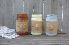 3 large mason jars, hand painted in chocolate brown, grey and ivory, lightly distressed and embellished with burlap, jute, and a burlap flower, with a protective coating. They are not painted on the i