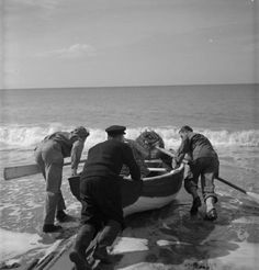 Pfc George W Burnett (left, of Route 5, Spartanburg, South Carolina) and Pfc Harris L Whitwell (left, of Main Street, Rogersville, Tennessee) help local fisherman Tom Swaffield to launch his rowing boat in the Dorset sunshine. Tom is taking the GIs out to see his lobster pots.