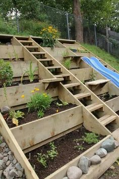Love this idea for a terraced hillside - planter beds, stairs, and slide.  Brilliant!