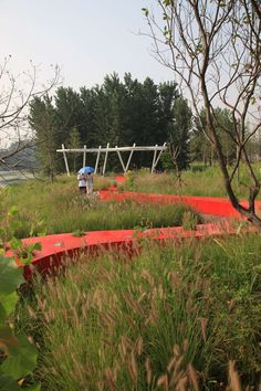 "Against a background of natural terrain and vegetation, is a ""red ribbon"" spanning five hundred meters, which integrates the functions of lighting, seating, ..."
