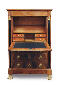 An extraordinary Empire secretaire German, c. 1810. Walnuttree with rootwood, veneered. Bronze applications with lions heads, flowers and caryatides above ebonised pilaster. 3 drawers bottom on carved and gilded paw feet. The writing surface with leather, inside compartments with 4 small drawers. Rest., additions. H. 150 cm, w. 95 cm, d. 50 cm.