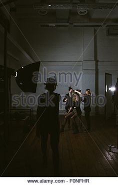 Make up artists preparing female fashion model for photo shooting in professional studio Stock Photo