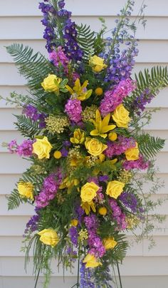 """An eye-catching, easel design brimming with hybrid delphinium, """"stock"""" flower, Asiatic lilies, roses and multiple type of foliage. Flowers at a funeral are the final opportunity to express you sentiments and flora often conveys what you are unable to say at the time."""