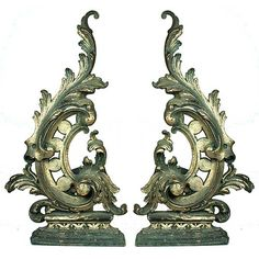 A dramatic pair of French antique andirons. In addition to no one being able to agree on one name for fireplace log rests, this style has been described as: rococo, scroll, flame and acanthus leaf. Whatever you choose to call them, they will definitely add glamour to your fireplace.
