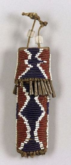 Southern Plains Beaded Whetstone Case, Kiowa, c. third quarter 19th century, the commercial leather capped form beaded overall with white and dark blue geometric elements on a wine red ground, remnant tin cone danglers, two large faceted clear beads on the hide strap, ht. 4 1/4 in.