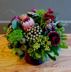pink protea, eucalyptus pods, brazillia, green tricks, silver brunia, fritillaria, and ranunculus, wrapped with a black ti leaf