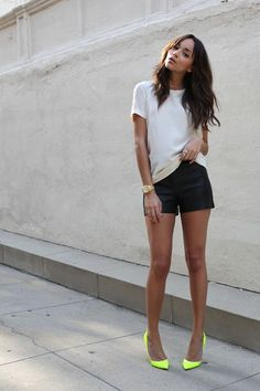 Pair a white crew-neck tee with black leather shorts for a standout ensemble. Take a classic approach with the footwear and rock a pair of neon yellow leather pumps.   Shop this look on Lookastic: https://lookastic.com/women/looks/crew-neck-t-shirt-shorts-pumps-watch-ring/12288   — White Crew-neck T-shirt  — Silver Ring  — Gold Watch  — Black Leather Shorts  — Green-Yellow Leather Pumps