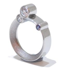 This sterling silver ring features three beautiful gemstones that cluster around the finger on an orbit, they are set on the side of the ring and glisten when catching the eye. The elevation of the crystals create stunning curvature when viewing from a birds-eye angle. the flashes of blue and white create energy throughout the ring.