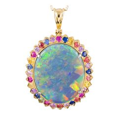 Set in yellow gold and surrounded by multi-colored sapphires which lend hints of color and draw out the flashes of luminous pastels exhibited by this magnificent stone. Opal Jewelry, High Jewelry, Turquoise Jewelry, Pendant Jewelry, Jewelry Accessories, Jewelry Necklaces, Jewelry Design, Pendant Necklace, Pendant Set