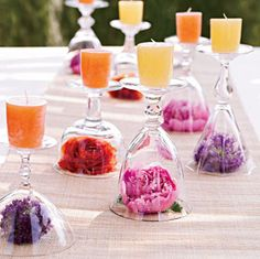 Place different wine glasses upside down, put a flower you like inside them and a candle on top.. Fantastic idea for dinner time or any other occasion!