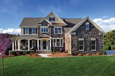 A rich stone exterior with a wrap-around front porch defined by graceful columns. The Ashville Model from Drees Homes. Churton Grove Community, near Raleigh, NC. - new homes