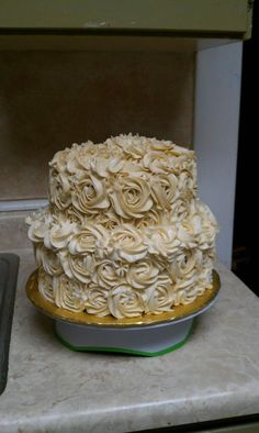 50th wedding anniversary cake. Chocolate bottom tier,golden vanilla top tier. Filled with swiss meringue butter cream. Civered in swiss meringue butter cream..icing flavors are cream of bouquet top,vaillna bottom ....: