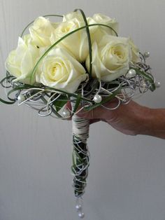 Modern bridal bouquet - In a frame of metal wire, wicker, bear grass and pearls are roses processed - The handle consists of stealing wrapped with wire, wicker and pearls | ART-NIVO bloem styling