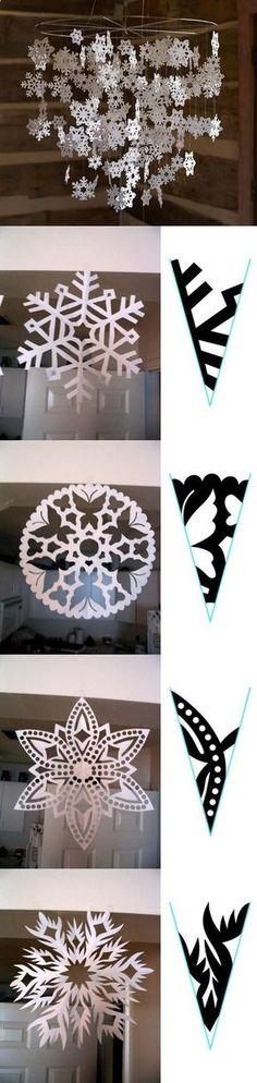 Ideia Faça Você Mesma (DIY) de móbile para festas de Frozen. São vários flocos de neve com formatos diferentes, todos feitos com papel recortado.