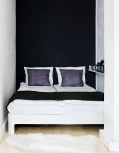 Tiny but stylist bedroom. Calm, graphic black wall.