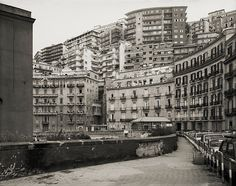 "Thomas Struth: Corso Vittorio Emanuele, Naples, 1989 ""Every expressive element is muted or cropped out, just up to the point where what's shown—say a baby-blue garbage bag tucked into a wire wastebasket that's nailed up against an old brick wall—seems about to speak""Jama P Prokryl NYRblog."