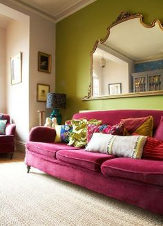 green walls, pink sofa, beautiful mirrow