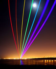 Yvette Mattern's Global Rainbow lasers on display across Whitley Bay, projected from St Mary's Lighthouse, North East England.