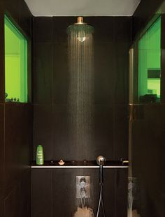 Go dark, even black, in a bathroom to contrast an all-white apartment like this one in Paris. To create a sense of visual connection from the loo to the rest of the 635-square-foot apartment, the architects set a colored window between the two rooms. They spent days making sure that the green transparency would meld nicely with the shade of green on the kitchen shelves.  Photo by: Céline Clanet