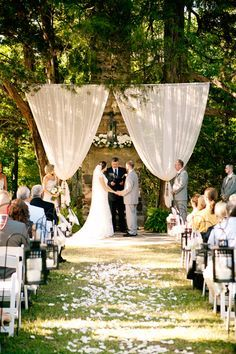 A chandelier, flowing fabric, and white flowers create a stunning backdrop for this rustic ceremony..