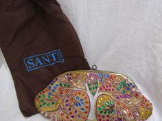 Great Condition Santi Gold Clutch With blue, purple, pink, green, orange and yellow gems. 12 x 6 inches. It has a hidden strap. We stand behind all our products and want to develop a successful relationship with all or our Etsy customers. We have provided information and photos for your benefit. Please ask all questions prior to making a purchase. If you purchase an item and feel that it is not as described, please contact us immediately. We will make every effort to make you happy. Any…