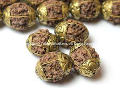 Nepal tibetana Natural Rudraksha Perlas con hilos de latón y gorras  Cantidad: 4 granos  Cada grano varía ligeramente debido a las calidades de semilla natural y naturaleza hecha a mano de la partida  Hechos a mano en Nepal  Artículo # B2500-4 Tamaño: Aproximadamente 16-18mm de ancho x 19-23mm de largo (orificio al agujero) Pulgadas de aproximadamente.70.63 ancho x.77 .90inch largo (orificio al agujero)   Póngase en contacto con nosotros si tiene cualquier duda. Gracias.  Me gusta nuestro…