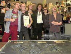 British heavy metal rock group 'Def Leppard' pose 05 September 2000 with Brian May (3rd R) of the rock group 'Queen' before their handprints, which will be placed in the Rockwalk in Hollywood. From left are: Rick Allen, Phil Collen, Joe Elliot, May, Vivian Campbell and Rick Savage. (ELECTRONIC IMAGE) AFP PHOTO/Lucy NICHOLSON