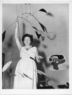 Peggy Guggenheim at Palazzo Venier dei Leoni with Alexander Calder, Arc of Petals (1941, PGC), Venice, early 1950s. Solomon R. Guggenheim Foundation. Photo Archivio CameraphotoEpoche. Gift, Cassa di Risparmio di Venezia, 2005. Behind her Jean Arp, Overturned Blue Shoe with Two Heels Under a Black Vault (1925, PGC).