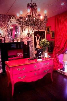 Fit for a pink (but not Barbie-esque) queen! Love the black chandelier and black and white wallpaper to help mute the pink.  I like the pink dresser and the mirror.