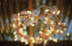 As luzinhas pisca-pisca podem fazer uma linda guirlanda para iluminar a festa. Foram usadas flores de tecido e casulos de bicho-da-seda