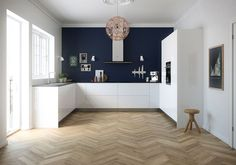 Mur bleu navy, parquet chevrons cuisine blanc mat, façades 19 mm d'épaisseur, bords arrondis. Prix : 3565 euros.  Kvik modèle Senti