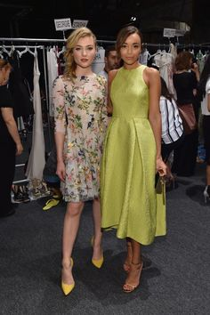 Skyler Samuels wears a floral embroidered fit and flare dress by Monique Lhuillier and yellow pointed-toe pumps. Ashley Madekwe wears a chartreuse jacquard sleeveless tea length dress, metallic clutch, and metallic sandals