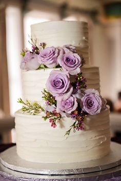 A rustic, textured three tier wedding cake with beautiful lavender roses