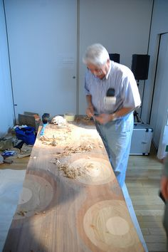 Craftsman's hands carving Ripples bench by Toyo Ito