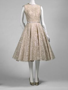Woman's Dress and Belt  Designed by Norman Norell, American.. Made by Traina-Norell. Sold by the Tribout Shop Date: 1954 Medium: Sized machine-made cotton lace with machine-appliquéd iridescent acetate strips, iridescent acetate sequins, silk taffeta